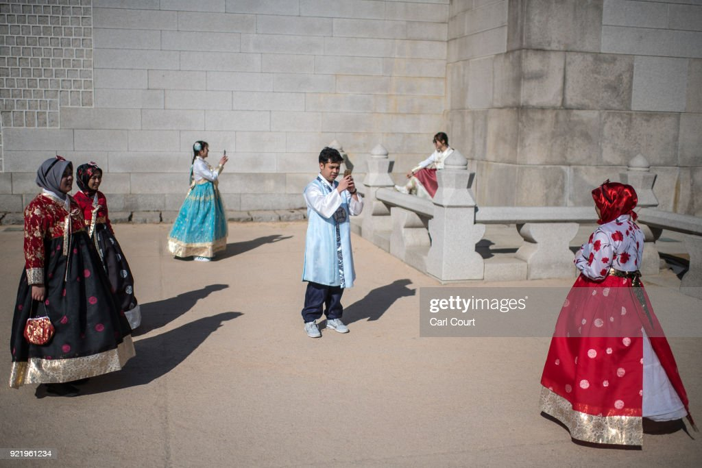 Tourists wearing traditional Korean Hanbok dresses pose for photographs near Gyeongbokgung Palace on February 21, 2018 in Seoul, South Korea. With tourists visiting from around the world, leaders from South Korea's capital as well as GyeongGi and Gangwon Provinces have agreed to work together to support the PyeongChang Olympic Games and to invigorate regional tourism.