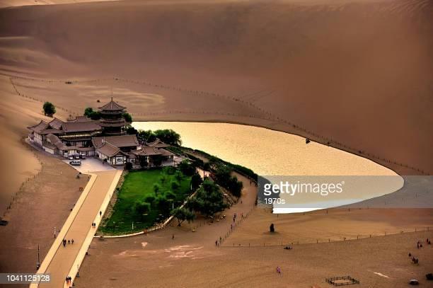 観光客は、オアシスの砂漠のザワザワさせる砂丘 (mingshashan) 中国、甘粛省敦煌の三日月湖を訪れていた - シルクロード ストックフォトと画像