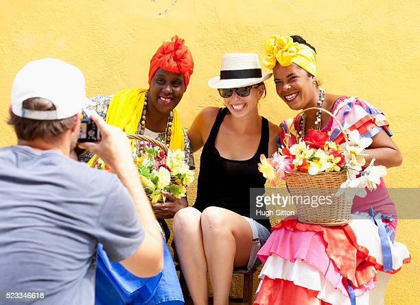 tourists with flower ladies. havana. cuba. - hugh sitton stock pictures, royalty-free photos & images