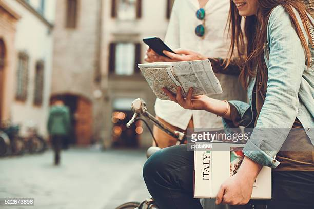 tourists with guide and map in alleys of italy - toerist stockfoto's en -beelden