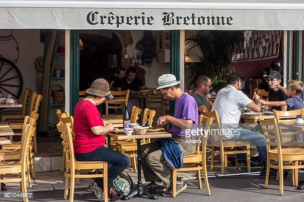 Tourists with hats eating Breton galettes at Creperie Bretonne in France