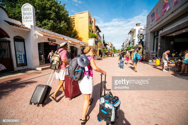 Tourists with luggage walking on 5th Avenue, Playa Del Carmen, Mexico