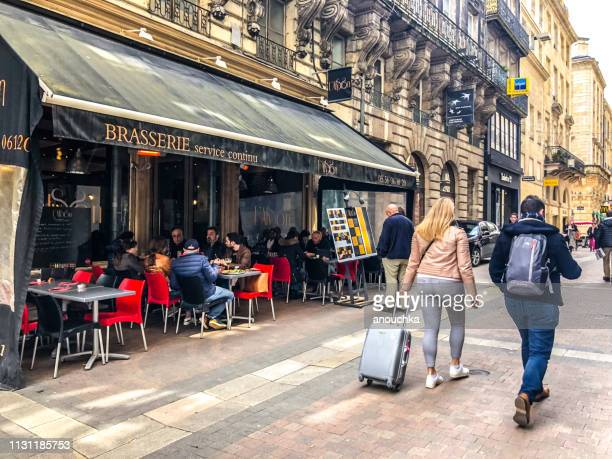 tourists with luggage walking through bordeaux, france - brasserie stock photos and pictures