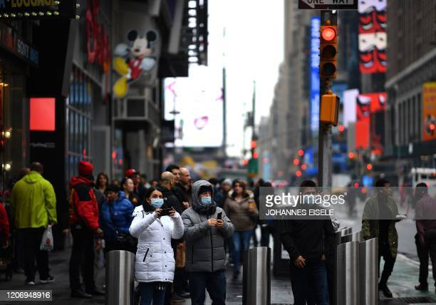 Tourists with protective face masks walk through Times Square on March 13 2020 in New York City The World Health Organization said Friday it was not...