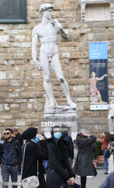 Tourists with protective mask visit Florence on February 25, 2020 as Tuscany reported its first two cases of COVID-19. - Italy's new coronavirus...