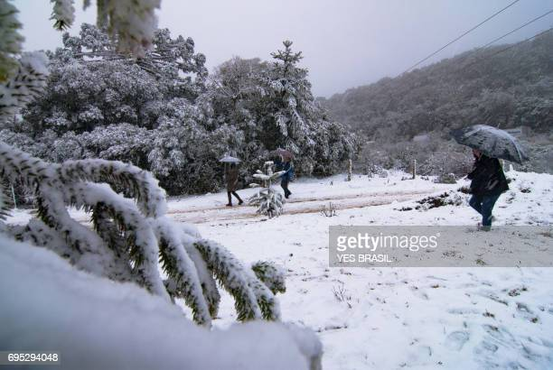 Tourists with their umbrellas, walk and play in the snow in Brazil