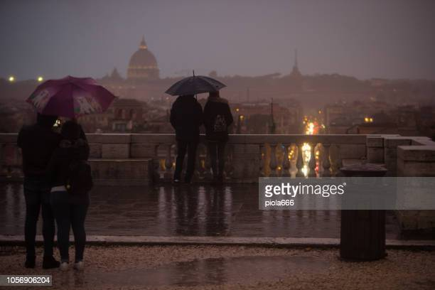tourists with umbrellas during a rainy day in rome, enjoying the view from pincio to piazza del popolo, with saint peter dome far on the horizon - tempesta foto e immagini stock