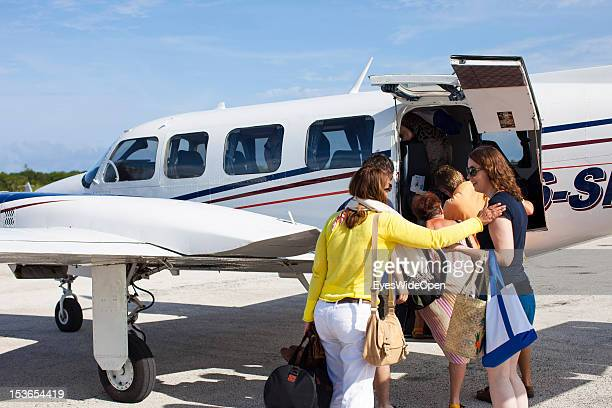 Tourists young woman are boarding at a Piper a private charter aircraft at Cat Island Airport on June 15 2012 in Cat Island The Bahamas