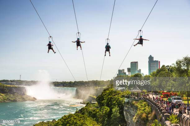 tourists zipline in niagara falls ontario canada - niagara falls stock pictures, royalty-free photos & images