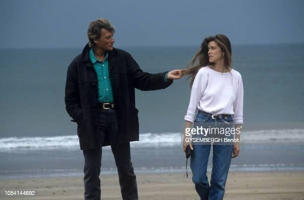 """Tournage de l'émission """"Embarquement immédiat"""" en Irlande. Mai 1987. Johnny HALLYDAY tenant une mèche de cheveux de Corynne CHARBY, tandis qu'ils..."""