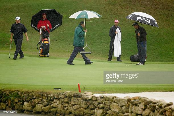 Tournament Administrator Paul Carrigill helps remove water from the ninth green after play was suspened due to heavy rain during the sixth round of...