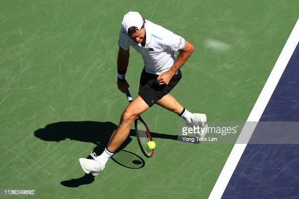 Tournament director Tommy Haas returns a shot from between his legs as he plays with John McEnroe against Novak Djokovic of Serbia and Pete Sampras...