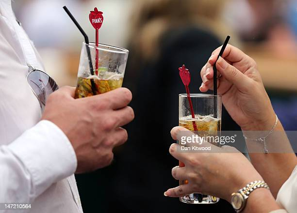 Tournament goers enjoy a glass of Pimms on day three of the Wimbledon Lawn Tennis Championships at the All England Lawn Tennis and Croquet Club on...