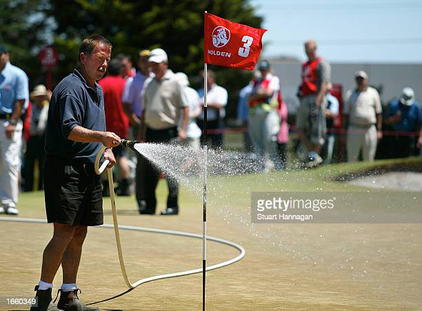 Tournament groundstaff water the third green shortly before the cancellation of the first round of the Holden Australian Open at the Victoria Golf...