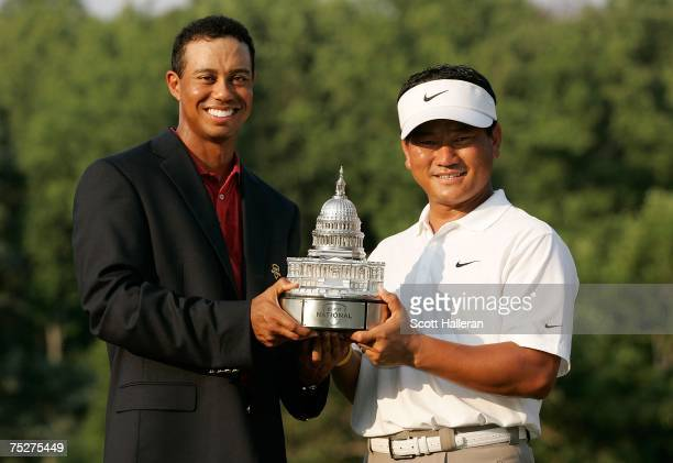 Tournament host Tiger Woods presents KJ Choi of South Korea with the winners trophy after his threestroke victory at the ATT National at...