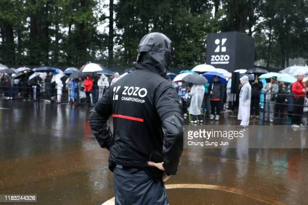 A tournament staff stands in the rain to organise spectators queuing for shuttle buses in front of the gate after the second round of the Zozo...