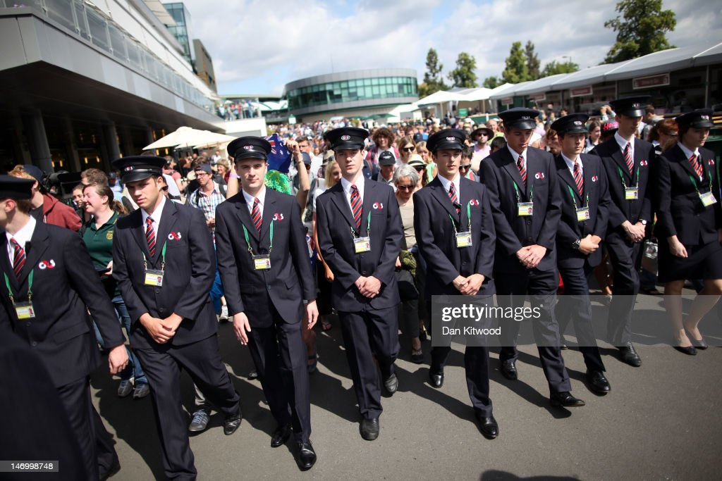 Tournament stewards escort the fans into the grounds on day one of the Wimbledon Lawn Tennis Championships at the All England Lawn Tennis and Croquet Club on June 25, 2012 in London, England.
