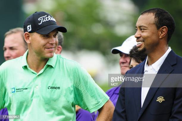 Tournament winner Bill Haas talks with tournament host Tiger Woods during the trophy ceremony of the AT&T National at Congressional Country Club in...