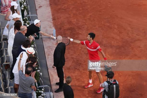 Tournament winner Novak Djokovic of Serbia passes his racquet to a fan as he celebrates after winning his Men's Singles Final match against Stefanos...