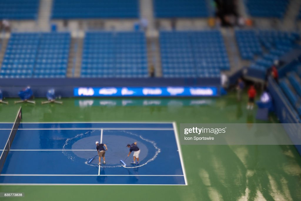 Tournament Workers Try To Squeegee The Tennis Court After Multiple