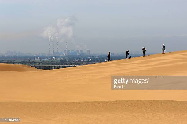 Toursits walk on the dunes near a power plant in Xiangshawan Desert also called Sounding Sand Desert on July 17 2013 in Ordos of Inner Mongolia...