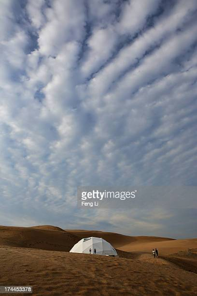 Toursits walk past a toilet in Xiangshawan Desert also called Sounding Sand Desert on July 17 2013 in Ordos of Inner Mongolia Autonomous Region China...