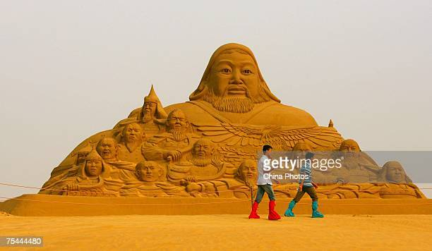 Toursits walks past a sand sculpture of Genghis Khan as they tour the Xiangshawan also called Resonant Sand Bay on July 16 2007 in Baotou of Inner...