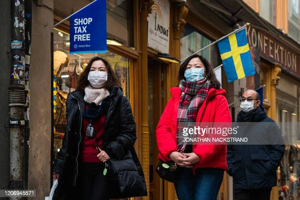 Toursits wear protective face masks due to the new coronanvirus COVID-19 as they visit the old town in Stockholm on March 13, 2020.
