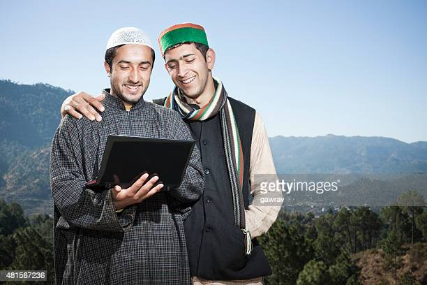 tow happy friends from different cultures of india using laptop. - hinduism stock pictures, royalty-free photos & images