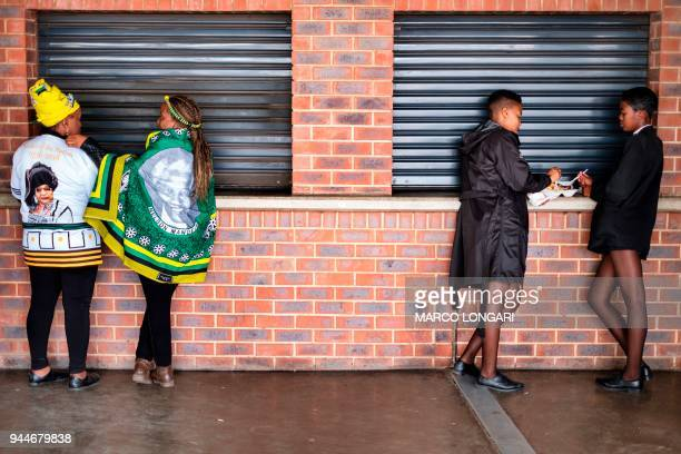 TOPSHOT Tow schoolgirls have a snack as two women wearing African National Congress regalia pause at the Orlando stadium in Soweto Johannesburg on...