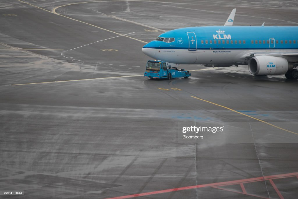 A tow tractor guides a passenger aircraft operated by KLM, the Dutch arm of Air France-KLM Group, on the tarmac at Schiphol airport in Amsterdam, Netherlands, on Tuesday, Aug. 15, 2017. Delta Air Lines Inc., China Eastern Airlines Corp. and Air France-KLM Group are reaching for their checkbooks to forge a deeper global alliance. Photographer: Jasper Juinen/Bloomberg via Getty Images