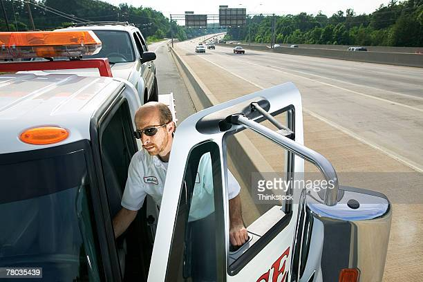tow truck driver getting into truck - tow truck stock pictures, royalty-free photos & images