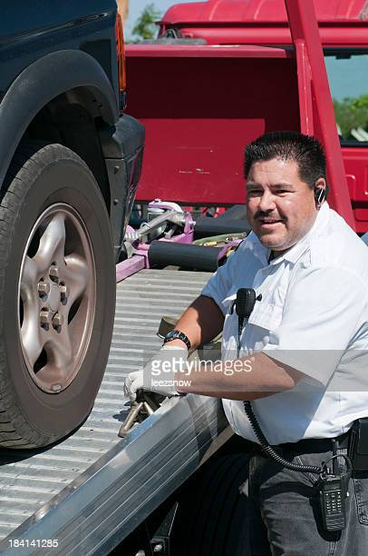 tow truck driver hauling a vehicle on a flatbed - tow truck stock photos and pictures