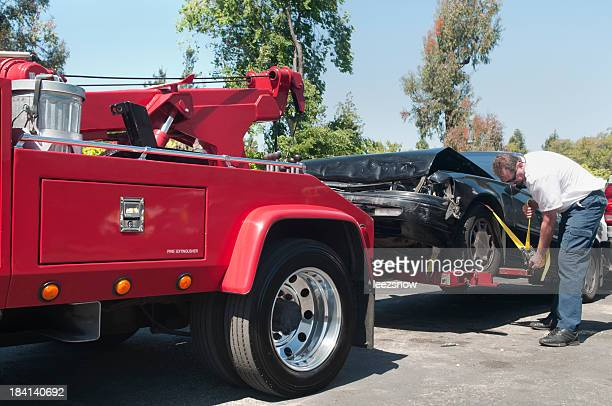 tow truck driver hauling a wrecked car - tow truck stock pictures, royalty-free photos & images