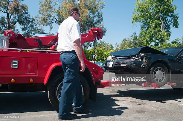 Tow Truck Driver Lifting a Wrecked Car