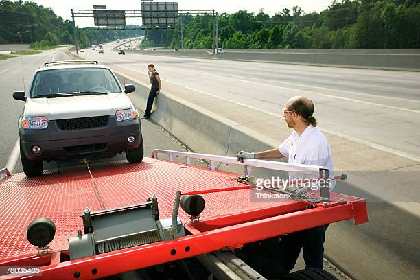 tow truck driver loading car - tow truck stock pictures, royalty-free photos & images