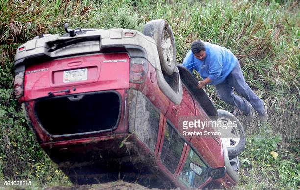 Tow truck driver Miguel Flores 34 of Ojai jumps from an overturned Chevrolet Trailblazer on Highway 33 north of Ventura The driver of the SUV Danelle...