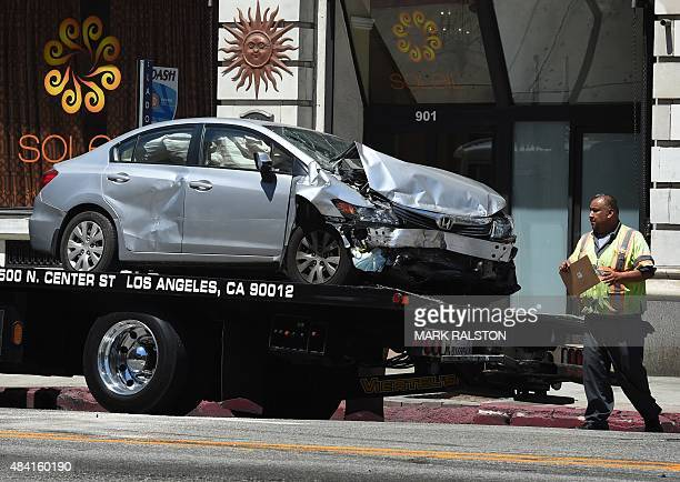 A tow truck drivers walks past the damaged car after its driver was arrested on suspicion of felony hitandrun after injuring six people in two...