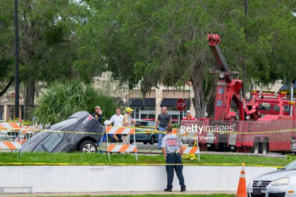 tow truck extracts car from sinkhole - cave in collapsing stock photos and pictures