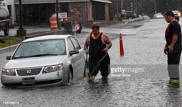 Tow truck operator get chain ready to tow elderly couple out of flooded street at 700 Broadway in Malden after sudden rain deluge caused flashed...