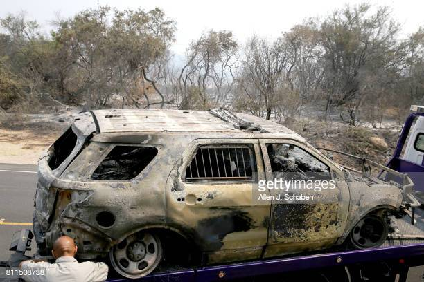 A tow truck operator secures the scorched remains of a Santa Barbara County Sheriff's Vehicle on Highway 154 east of Cachuma Lake The Deputy was not...