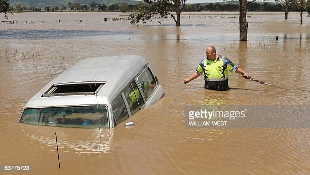 A tow truck operator wades into the flood waters to tow a fourwheel drive to dry ground some 80 kilometres west of Brisbane on November 21 as flash...