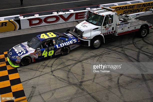 A tow truck pushes the Lowe's Chevrolet driven by Jimmie Johnson off the track after Johnson won the NASCAR Sprint Cup Series AAA 400 at Dover...