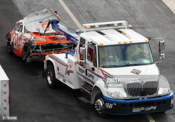 A tow truck removes Joey Logano's heavily damaged Home Depot Chevrolet off the track after it was involved in a wreck during the NASCAR Sprint Cup...