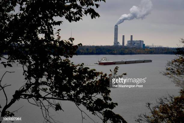 A towboat pushing barges full of corn heads north on the Mississippi near Alton Ill The coal fired energy plant in the background is the Sioux Power...