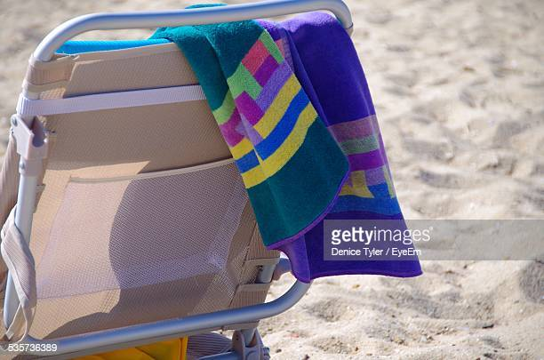 Towel Handing On Back Of Sunlounger Against Beach Sand