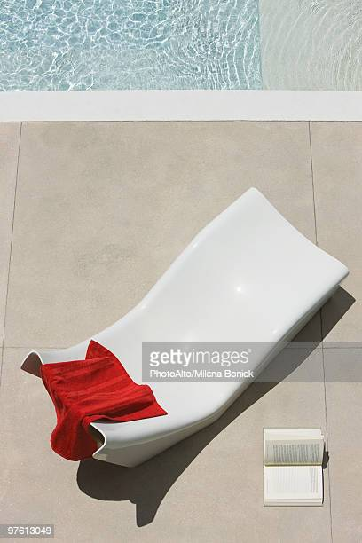 Towel left on poolside deckchair, open book lying on ground nearby