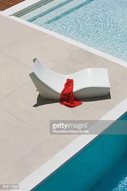 Towel left on poolside deckchair