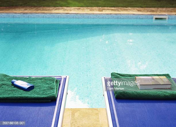 Towels, book and sun cream placed on sun loungers at edge of pool