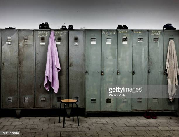towels hanging from lockers in locker room - locker room stock pictures, royalty-free photos & images